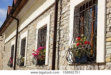 Flowers in front of the window. Pelargonium on fasede building. A window in an old building in jail