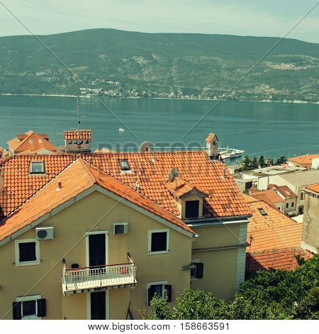 Herczeg Novi, Montenegro. Red roofs blue sea green plants - ideal summer landscape. Herceg Novi is a coastal town in Montenegro located at the entrance to the Bay of Kotor. Square toned image
