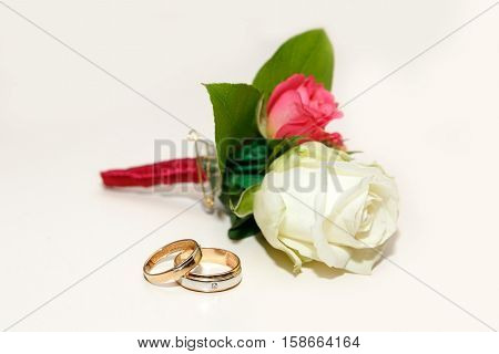 beautiful groom's boutonniere of white and red roses and wedding rings on a white table