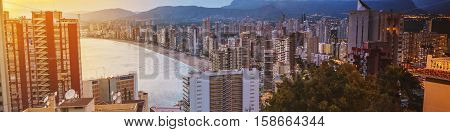Aerial view of summer resort Benidorm, Spain with beach and famous skyscrapers. City has three major beaches of the maximum quality standard. Sunset cloudy sky, day to night, illumination in Benidorm