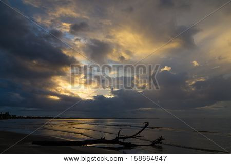 Dramatic sunset on the ocean coast - fantastic clouds are illuminated by the sun. Fiji.