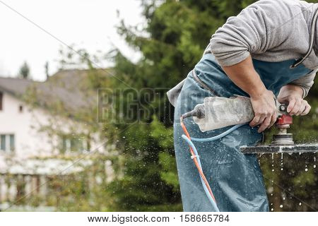 handyman working with grinding machine on a stone plate