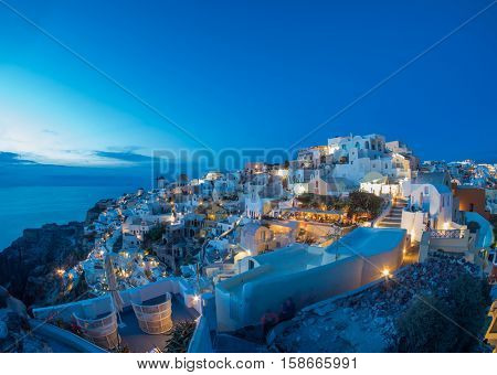 cityscape of Oia, traditional greek village of Santorini at sunset, Greece