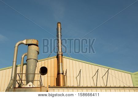 An industrial unit with a pipework system and metal exhaust stack against a blue sky.