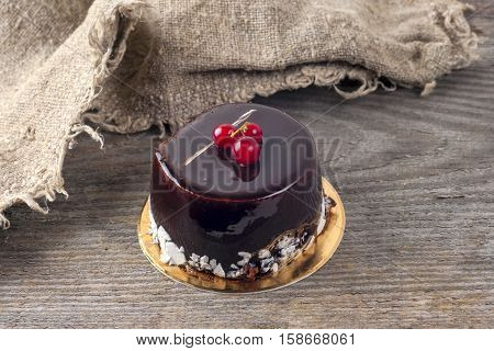 Delicious chocolate cake on plate on table on rustic wooden background