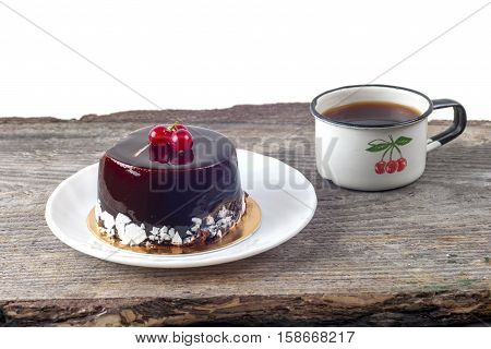 Delicious chocolate cake on plate and a cup of hot drink on table on rustic wooden background