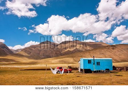 KUMTOR, KYRGYZSTAN - AUG 4, 2013: Landscape with farmer's trailer and car in a valley between the mountains of Central Asia on August 4, 2013. Kyrgyzstan's population is 5.4 million