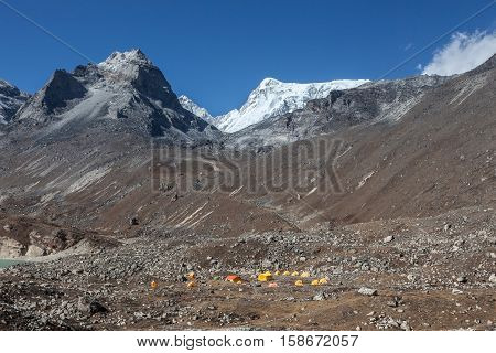 Base Camp In High Himalayan Mountains, Everest Area In Nepal. Yellow Tents On Rocky Ground Under Sno