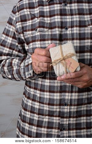 Closeup of a man in a flannel shirt holding a small fabric wrapped present