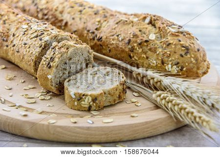 Rich in fiber dark bread on a wooden board with ears of corn of rye
