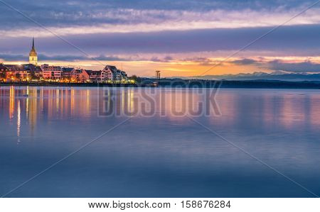 Bodensee lake in the sunrise colors - Enchanting landscape with a colorful sky reflected in the water of the Bodensee lake as the sun is coming up over Friedrichshafen town Germany.