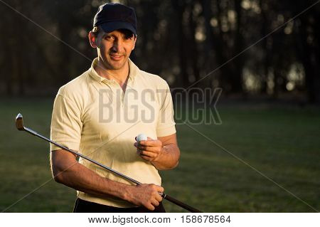 Handsome smiling golf player is holding a golf ball and the putter.