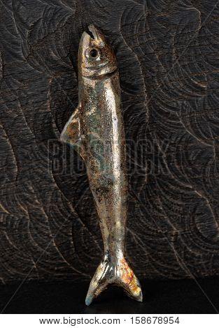 Handmade clay fish shot against wood surface