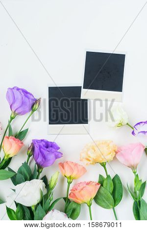 Pink, white, orange and violet eustoma flowers with two instant photos