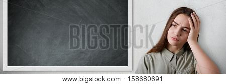 Portrait of beautiful smart schoolgirl with long dark hair standing near the blackboard holding her head with her hand being tired of the lessons