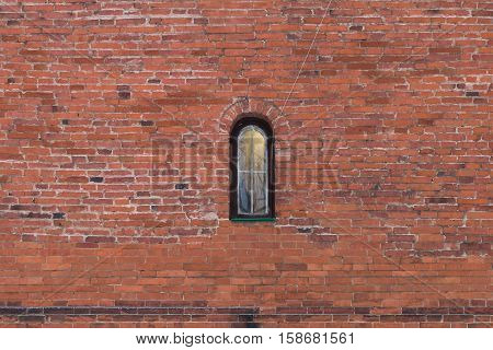 Texture of old brick wall with a small window. Red brick wall background with small window.