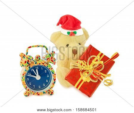 Alarm clock and teddy bear classic soft toy rigged out as Santa Claus sitting with gift box isolated over white. Christmas and New Year time.
