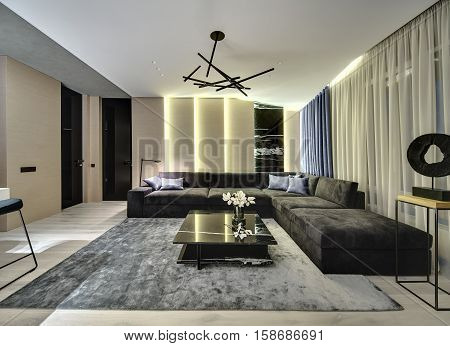 Room in a modern style with wooden walls with a marble part. There is a dark sofa, black marble table with flowers, gray carpet, large window with curtains, doors, wooden stand with decorative figure.
