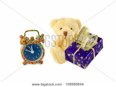 Teddy bear classic soft toy sitting with blue gift box and alarm clock isolated over white. Front view. Time to make gifts.