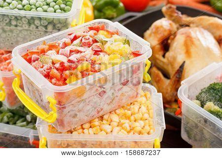 Frozen foods vegetables cook in plastic containers fried chicken in pan. Healthy freezer meals.
