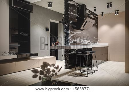 Modern style kitchen island with a black marble wall with a kitchen hood and a white tabletop with a stove and a sink. There are wooden lockers, black stools, decorations, conditioner, fireplace.