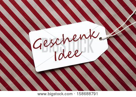 German Text Geschenk Idee Means Gift Idea. One Label On A Red And Brown Striped Wrapping Paper. Textured Background. Tag With Ribbon.