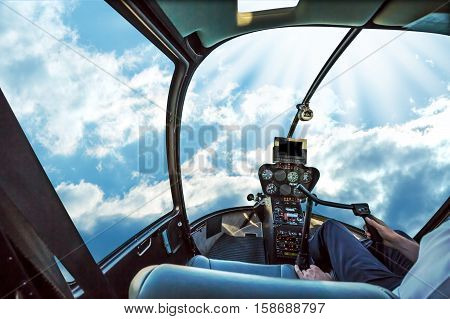 Helicopter cockpit flies in San Francisco Financial District Downtown, California, United States, with pilot arm and control board inside the cabin.Helicopter cockpit in a cloudy blue sky ad day.