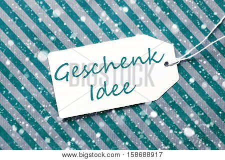 German Text Geschenk Idee Means Gift Idea. One Label On A Turquoise Striped Wrapping Paper. Textured Background With Snowflakes. Tag With Ribbon.