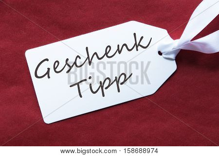 German Text Geschenk Tipp Means Gift Tip. One White Label On A Red Textured Background. Tag With Ribbon.