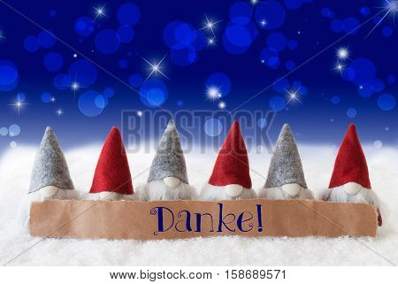 Label With German Text Danke Means Thank You Christmas Greeting Card With Gnomes. Sparkling Bokeh And Blue Background With Snow And Stars.