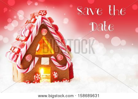 English Text Save The Date Gingerbread House In Snowy Scenery As Christmas Decoration. Candlelight For Romantic Atmosphere. Red Background With Bokeh Effect.