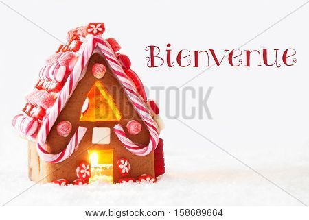 Gingerbread House In Snowy Scenery As Christmas Decoration With White Background. Candlelight For Romantic Atmosphere. French Text Bienvenue Means Welcome