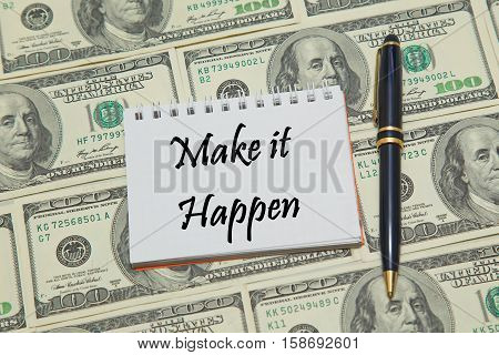 Notebook page with text MAKE IT HAPPEN on dollar background