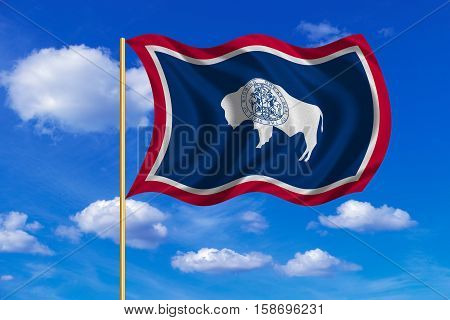 Flag of the US state of Wyoming. American patriotic element. USA banner. United States of America symbol. Wyomingite official flag on flagpole waving in the wind blue sky background. Fabric texture, 3D rendered illustration