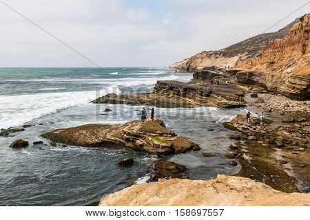 POINT LOMA, CALIFORNIA - APRIL 4, 2016: People explore the tide pool area on a cloudy day in part of the Cabrillo National Monument in San Diego, California.
