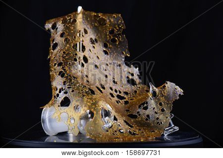 Close up detail of marijuana oil concentrate aka shatter isolated on black background with glass rig and dabbing tools