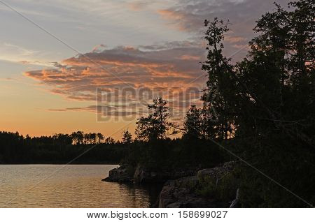 Silhouettes and Red Clouds at Sunset on Kawnipi Lake in Quetico Provincial Park in Ontario