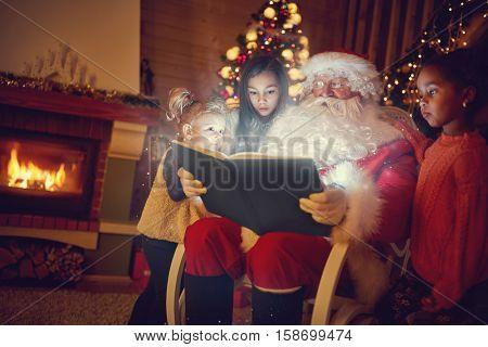 Santa Claus with three multi ethnic girls reading magic Christmas fairy tale