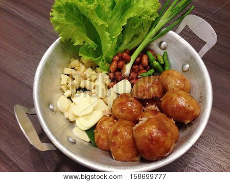 Isaan sausage, Thai Northeastern sausage, Thai pork mix rice sausage served in dish on wooden table background