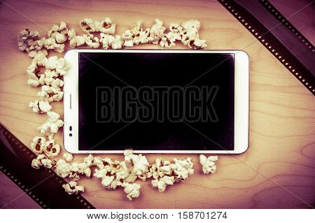 Smartphone on wood with attributes of cinema. Visual metaphor for internet content - films and media on a mobile device.