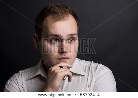 Young handsome minded man thinking to find way to solve problem