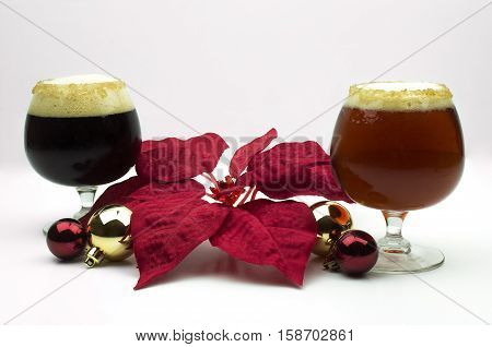 Christmas Ales sitting among bulb ornaments and poinsettia