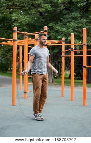 Handsome young muscular sports man skipping rope outside. Fit, fitness, exercise, workout and healthy lifestyle concept.