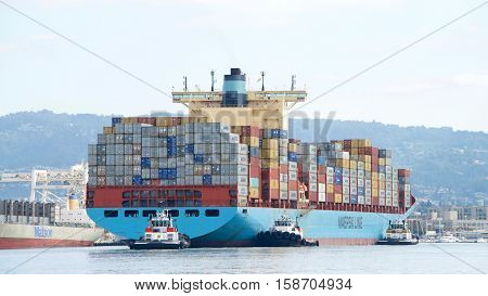 Oakland CA - October 11 2016: Multiple tugboats assist cargo ship GUNVOR MAERSK to maneuver into the Port of Oakland the fifth busiest port in the United States.