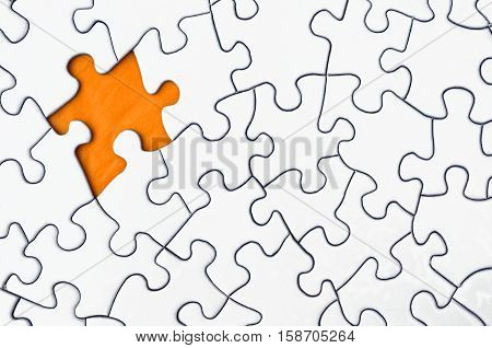 A top view image of a white jigsaw puzzle with one piece missing.