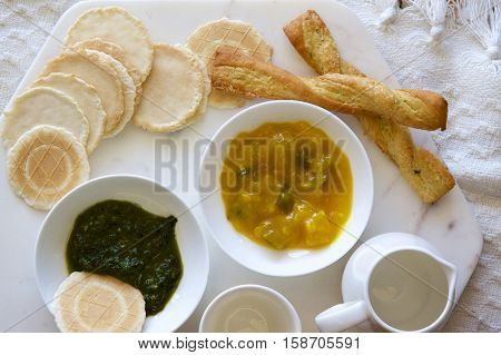 Pickles and pesto with savoury biscuits in a board.