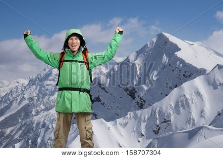 Happy male mountain climber with arms raised above the head. In the background the high mountains.