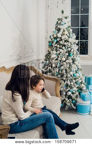 family phone talking - cute little boy and his mother are sitting on the sofa and talking by cell phone