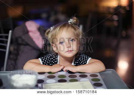 Elementary age girl sitting at the table in cafe. Girl waiting for her order. Girl is bored sitting at the table. Facial closeup portrait of a little girl in a cafe