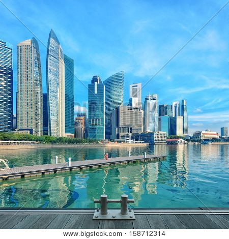 Singapore central quay with water on foreground. Modern city architecture at sunny day with wooden decks on foreground